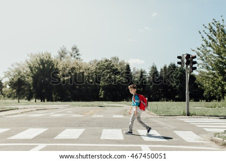 Schoolboy crossing road on way to school