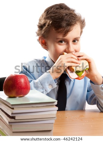 Schoolboy having a sandwich and an apple during his lunch break - stock photo