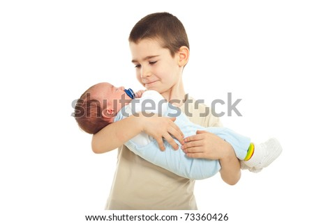 Schoolboy holding his newborn baby brother isolated on white background
