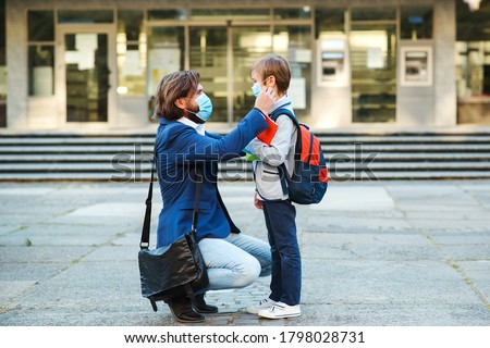 Schoolboy is ready go to school. Dad putting on a protective mask on his son's face. Cute boy with a backpack. Back to school concept. Medical mask to prevent coronavirus. Coronavirus pandemic Foto stock ©