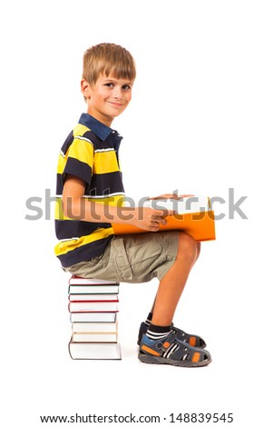 Schoolboy is sitting on books isolated on a white background