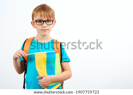 Schoolboy learning ukrainian language. Cute boy with backpack holding ukrainian flag. People, education, learning and school concept. Little student holding books, isolated on white. Photo stock ©