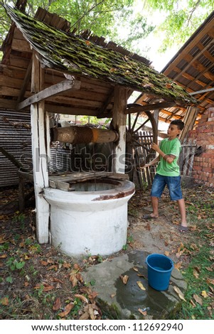 Schoolboy outdoor getting water from a vintage wooden well with pulley