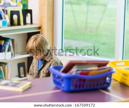 Schoolboy reading book in library