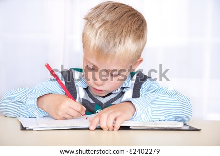 schoolboy sitting at a desk with a notebook and pencil and write. portrait, close up