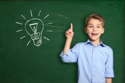 Schoolboy standing near blackboard with light bulb