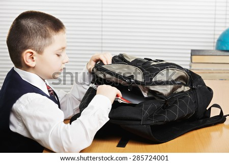 Schoolboy taking books out of bag in classroom  Stockfoto ©