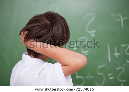 Schoolboy thinking while scratching the back of his head in front of a chalkboard