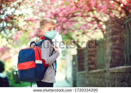 Schoolboy wearing face mask during corona virus outbreak. Boy going back to school after covid-19 quarantine. Boy in safety mask for coronavirus prevention. Kid with backpack going to school.