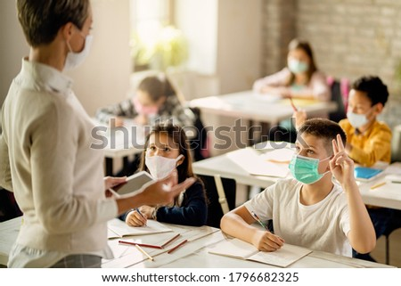 Schoolboy with face mask raising hand to answer the question during a class in the classroom.