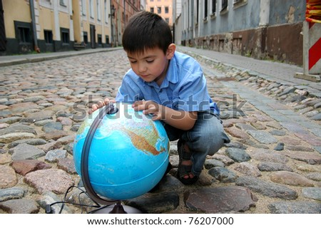 Schoolboy with globe on the street