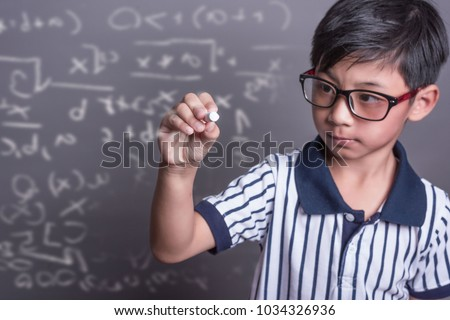 schoolboy writing math formula on  blackboard.asian grade school student solving a geometry problem on chalkboard in math class, film grain tone