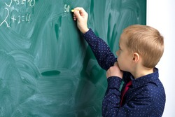 Schoolboy writing on chalkboard in classroom