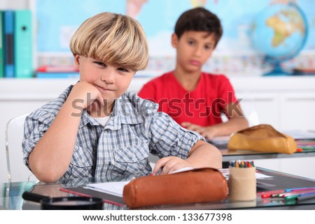 schoolboys seated at desk in classroom