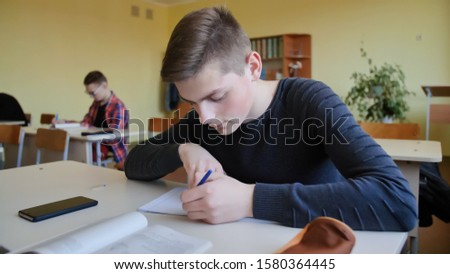 Schoolchild in class busy with work. Russian school.