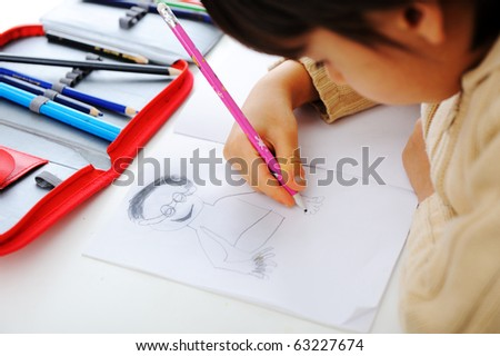 Schoolchild is drawing a man on his notebook with a pencil