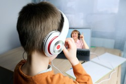 schoolchild, kid 6-7 years doing homework in front laptop, teacher on screen leads lesson on Internet, online conference, selective focus on headphones, concept of remote learning, lockdown covid-19