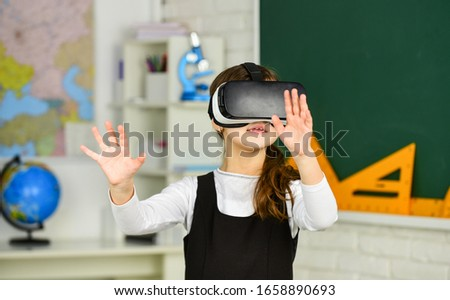 Photo of schoolchild using virtual reality. virtual reality headset. teenage schoolgirl in classroom. back to school. In a Computer Science Class. Works on a Programing Project. vr technology.