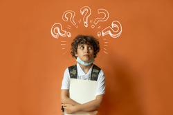 Schoolchild wearing a protective mask confused with question mark over the head isolated on a orange wall. Covid-19, coronavirus back to school concept.