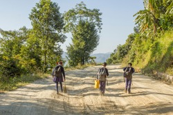 schoolchildren girl and boys go to school on a dirt road in the forest against the backdrop of the mountains