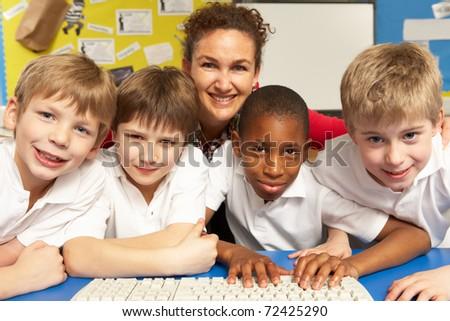 Schoolchildren in IT Class Using Computers with teacher