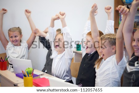 Schoolchildren showing success together in the classroom - stock photo