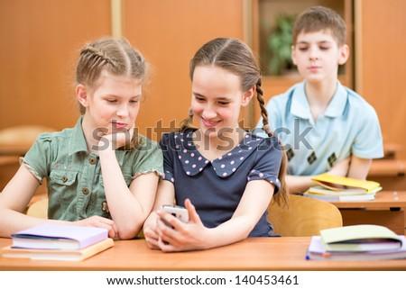 schoolchildren using mobile phone at lesson break