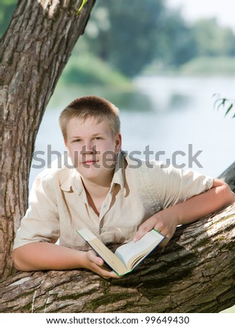 schoolchildren with the book in park on the bank of lake