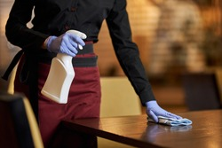Schooled waitress sanitizing table surface regularly with special spray
