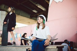 Schoolgirl after school. Portrait confident, cool young female skateboarder at outdoor skate park. Urban girl with skate board on half pipe ramp. lifestyle. Sports club for children. Skateboard club.