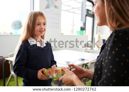 Schoolgirl at a primary school presenting a gift to her female teacher in a classroom, waist up, close up