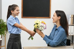 Schoolgirl congratulating her pedagogue with bouquet in classroom. Teacher's day
