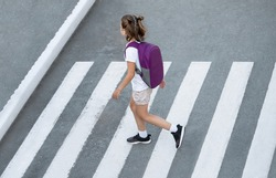 Schoolgirl crossing road on way to school. Zebra traffic walk way in the city. Concept pedestrians passing a crosswalk.  Stylish young teen girl walking with backpack. Active child. Top view
