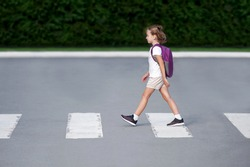 Schoolgirl crossing road on way to school. Zebra traffic walk way in the city. Concept pedestrians passing a crosswalk.  Stylish young teen girl walking with backpack. Active child