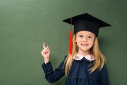 schoolgirl in graduation hat pointing at copy space next to chalkboard