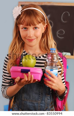 schoolgirl in the classroom holding lunch box,apple and bottle of water going to eat