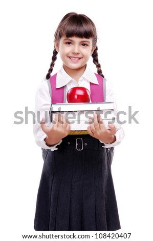 schoolgirl in uniform standing on white background and holding books and apple