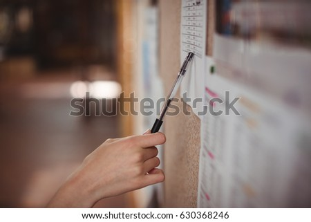 Schoolgirl looking at notice board in corridor at school Foto d'archivio ©