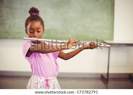 Schoolgirl playing flute in classroom at school