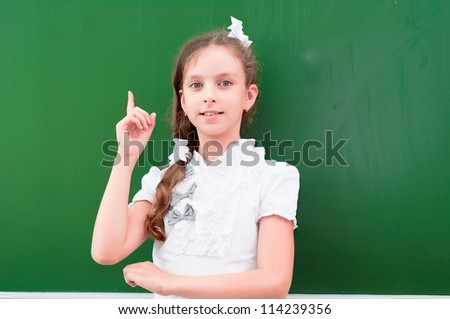 schoolgirl portrait near the blackboards, points finger up