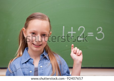 Schoolgirl raising her hand in front of a blackboard