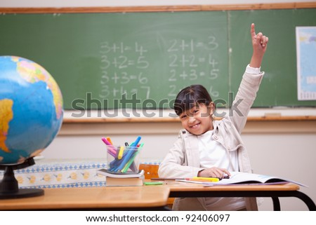 Schoolgirl raising her hand to answer a question in a classroom