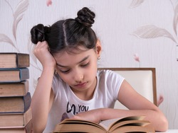 schoolgirl read book, young girl bored and tired of reading book at home. bored focused brainy girl nerd reading book learning grammar preparing final year exam test