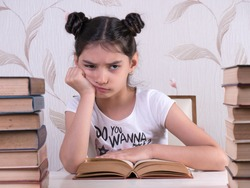 schoolgirl read book, young girl bored and tired of reading book at home. bored focused brainy girl nerd reading book learning grammar preparing final year exam test  tired of studying
