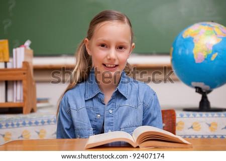 Schoolgirl reading a book in a classroom