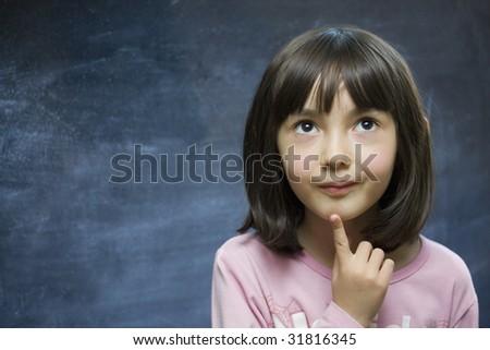 Schoolgirl stay near school blackboard. Close up.
