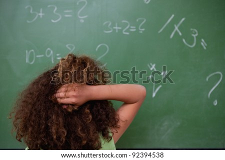Schoolgirl thinking about mathematics while scratching the back of her head in front of a blackboard