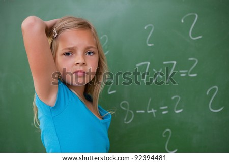 Schoolgirl thinking while scratching the back of her head in front of a blackboard