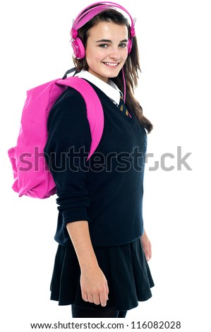 Schoolgirl with pink backpack and matching headphones enjoying music