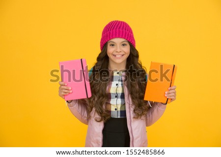 Schoolgirl with textbooks. Little smiling girl hold books. Future textbooks modern education. Textbook useful in learning environment. School creating textbooks generation. Active role in curriculum.